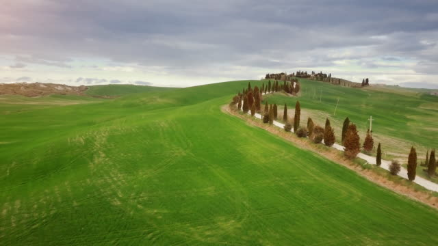 Classic Tuscan view: green hill and cypresses