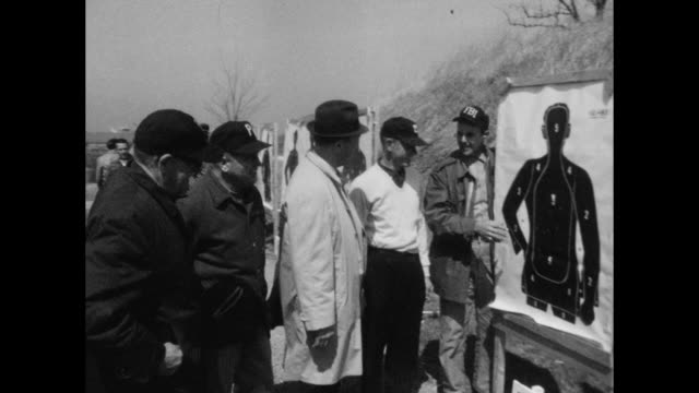 Classic vintage image of police recruits drawing pistols and shooting at targets at police academy firing range FBI agent gives instruction