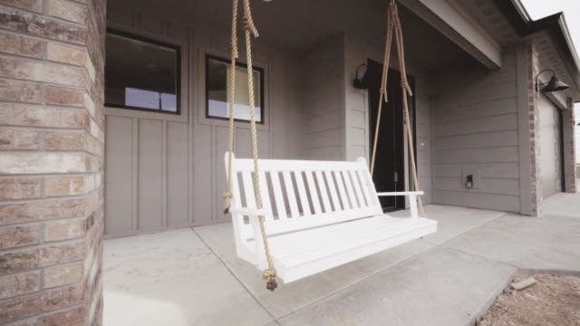 classic white front porch swing at a new custom home - veranda stock videos & royalty-free footage