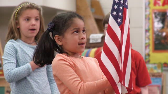 Classroom of young students holding American flag and reciting Pledge of Allegiance