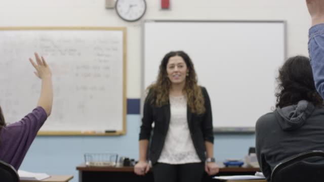 classroom raising hands as teacher stands in front of the class - aula video stock e b–roll