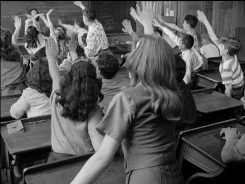 / classroom school children at desks raising hands woman teacher at blackboard / two boys whispering as teacher writes at blackboard / front view of... - bambino di età scolare video stock e b–roll