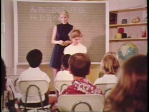 vidéos et rushes de classroom teacher calls for children to sit down / teacher wearing a mouth constume and children wearing ear costumes - 1972
