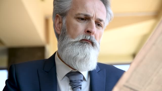 classy dressed senior businessman having good time in hotel lobby - beard stock videos & royalty-free footage