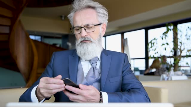 classy dressed senior businessman using smart phone - metrosexual stock videos & royalty-free footage
