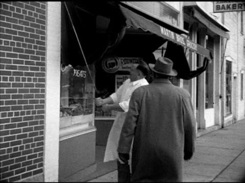 claude eames speaking w/ grocer reubin martin outside of store pedestrians on street bg grocery store wisconsin wi - lebensmittelhändler stock-videos und b-roll-filmmaterial