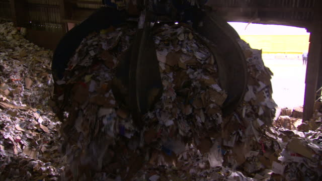 A claw crane dumps paper and paper products into a heap at a drop-off facility.