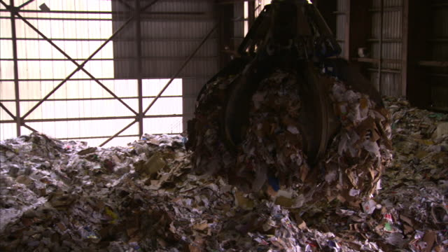 A claw crane lifts heaps of paper and paper products at a drop-off facility.