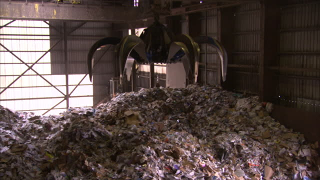 A claw crane operates in a paper collection facility.