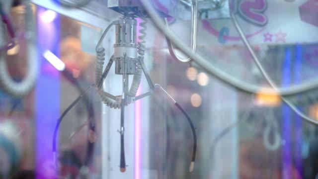 vidéos et rushes de jeu de griffes à une arcade dans l'action en mouvement. - fête foraine