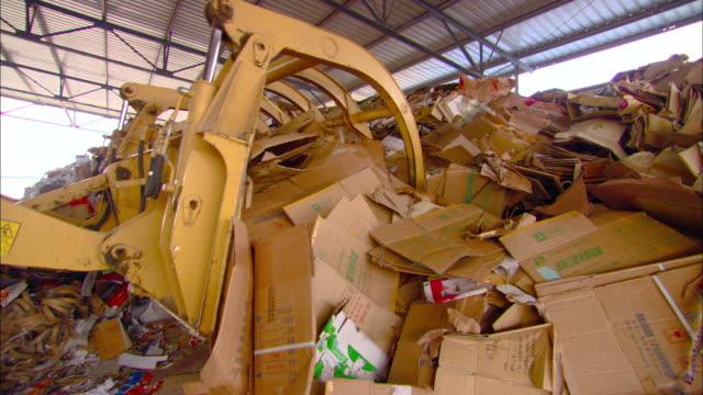 ms ts claw of excavator used to move heaps of cardboard at recycling center, beijing, beijing, china - bulldozer stock videos and b-roll footage