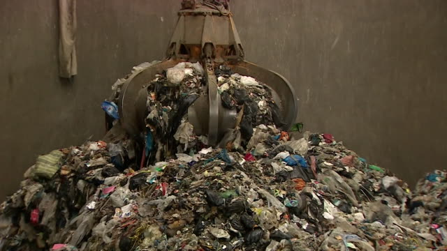 Claw picking up rubbish at waste management and recycling site in Bristol that turns domestic waste into energy