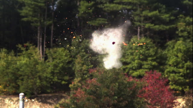 a clay pigeon disintegrates as it's hit by pellets. - clay pigeon shooting stock videos & royalty-free footage
