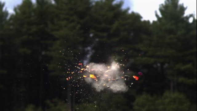 a clay pigeon disintegrates as it's hit by pellets. - tiro al piattello video stock e b–roll