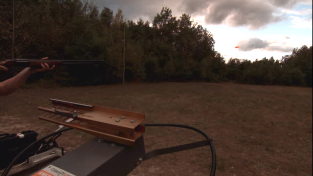 a clay pigeon flies into the air from a skeet shooter. - clay pigeon shooting stock videos & royalty-free footage