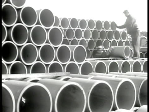 PIPES Clay pipe yard w/ pipes stacked men loading pipes onto truck rolling pipes off top of pile MS Stack of wide pipes CARPENTERS Men carry beams of...