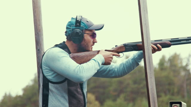 clay target shooter aiming and shooting - tiro al piattello video stock e b–roll