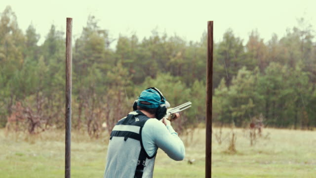 clay target shooter hitting the mark (slow motion) - tiro al piattello video stock e b–roll