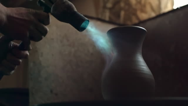vidéos et rushes de clay vase being dried with blowtorch flame - un seul objet