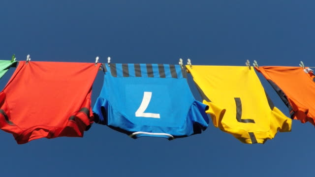 clean colourful sports shirts drying on a washing line. - washing line stock videos & royalty-free footage