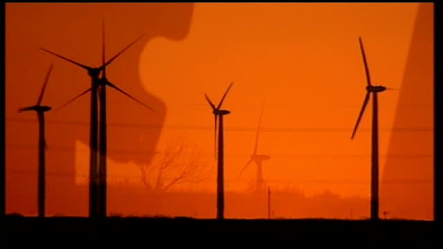 Clean energy boom in Texas EVENING Silhouette of wind turbines turning against orange sky and setting sun