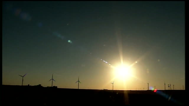 Clean energy boom in Texas Long Shot of turbines silhouetted against setting sun