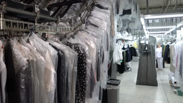 clean garments on conveyor belt at an industrial dry cleaning service - laundromat stock videos & royalty-free footage