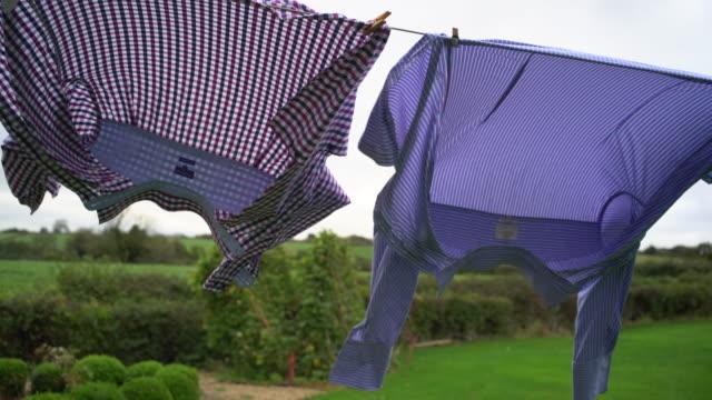 vídeos y material grabado en eventos de stock de clean mens shirts on the washing line. - hacer la colada