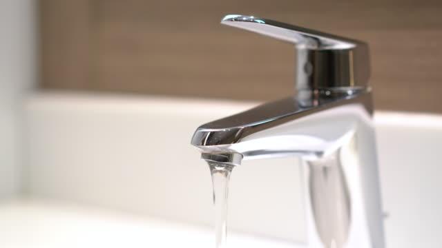 vídeos de stock, filmes e b-roll de 4k-limpa a água da torneira de torneira e pia no banheiro - domestic bathroom
