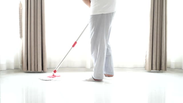 cleaner man cleaning tiled floor in the living room - housework stock videos and b-roll footage