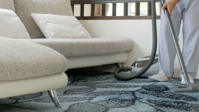 Cleaner vacuuming in living room