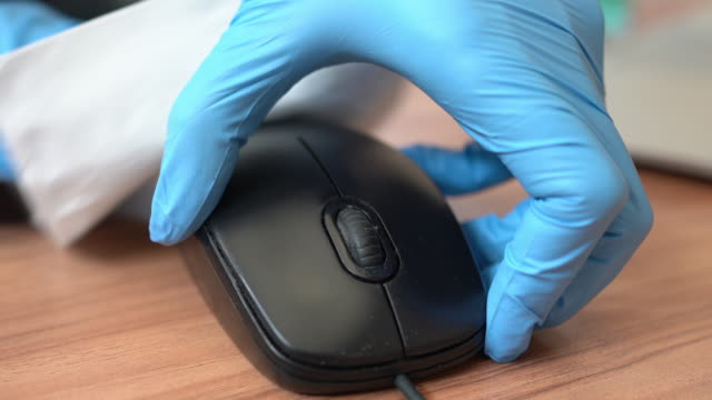cleaner wiping down computer mouse surfaces for cleaning covid-19 virus in office - dustman stock videos & royalty-free footage