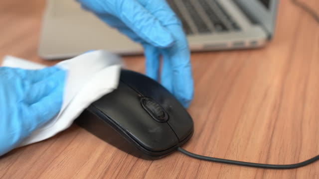 cleaner wiping down computer mouse surfaces for cleaning covid-19 virus in office - strofinare toccare video stock e b–roll