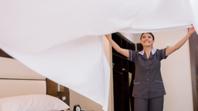 cleaner working at a hotel making the bed - lavori di casa video stock e b–roll