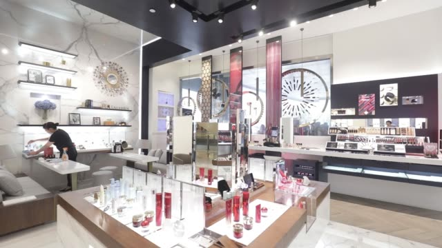 A cleaner works inside an Estee Lauder Companies Inc store in the Raffles City shopping mall in Shanghai China on Wednesday May 31 A sales assistant...