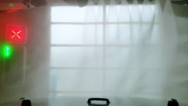 städar bilen på en biltvätt. visa från bilen genom vindrutan. - biltvätt bildbanksvideor och videomaterial från bakom kulisserna