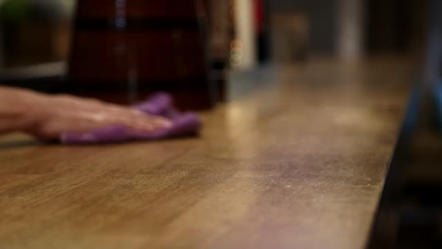 cleaning a wood table - limpiando una mesa de madera con un paño - madera material stock videos and b-roll footage
