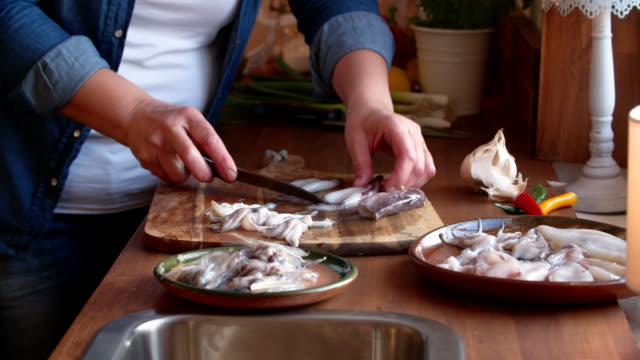 Cleaning and Cutting Fresh Squid on a Wooden Cutting Board