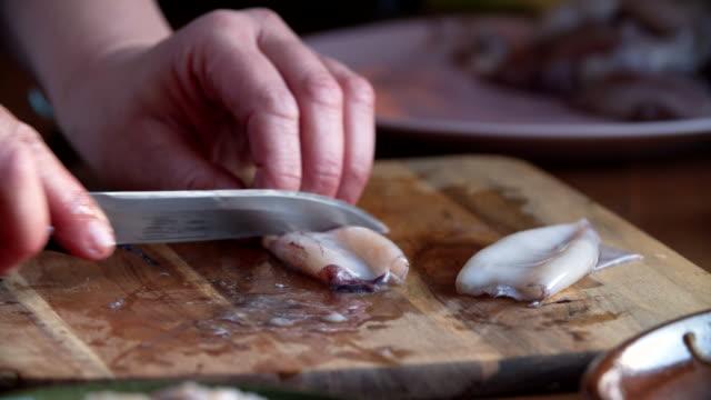 Reinigen en snijden van verse inktvis op een houten snijplank