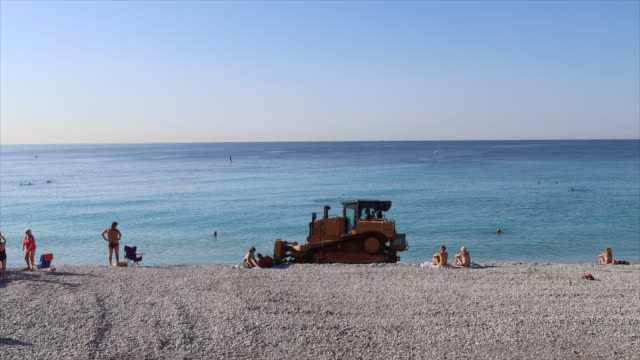 stockvideo's en b-roll-footage met cleaning and maintenance of nice beach with a construction machine - grondverzetmachine