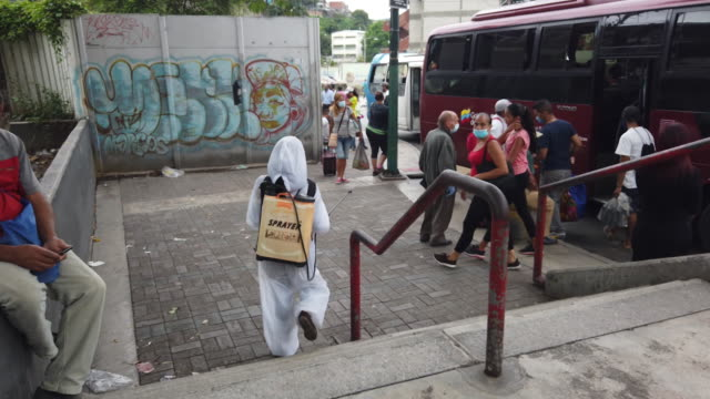 cleaning company employee disinfecting bus stop area during pandemic in petare, caracas, venezuela, on thursday, september 3, 2020. - spray stock videos & royalty-free footage