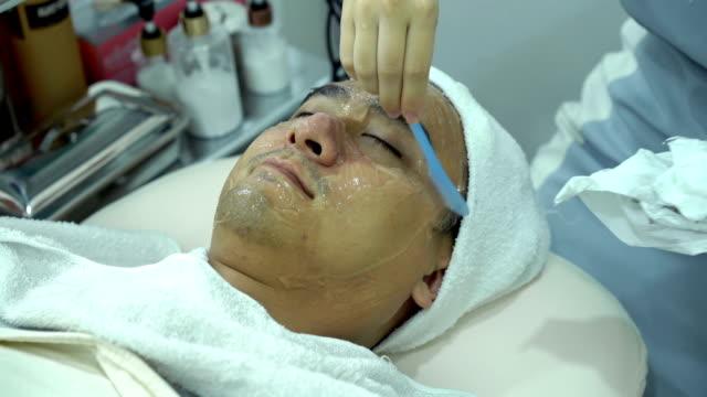 vídeos de stock, filmes e b-roll de 4k limpeza gel de refrigeração depois de fazer tratamento ipl de rosto masculino jovem na clínica de beleza - dermatologia