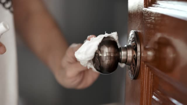 covid-19 : cleaning doorknob - strofinare toccare video stock e b–roll