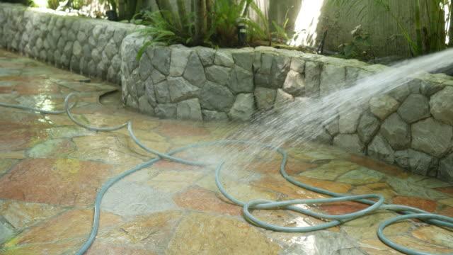 vídeos de stock, filmes e b-roll de limpeza de chão no jardim do spa - estampa de folha
