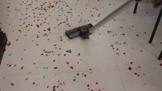 cleaning home floor with vacuum after party with confetti. - pavimento video stock e b–roll