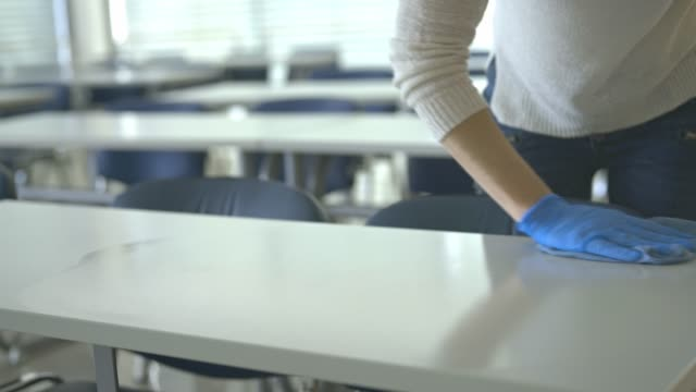 Cleaning lady disinfects tables in a school classroom during the quarantine period