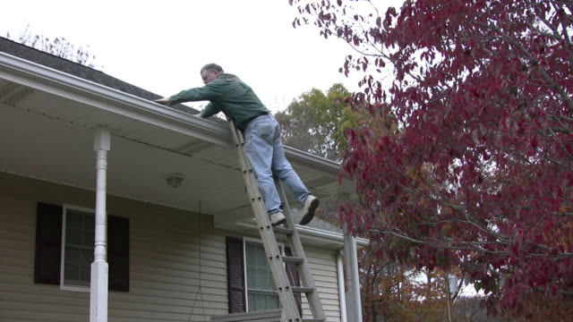 stockvideo's en b-roll-footage met cleaning out the gutters - ladder gefabriceerd object