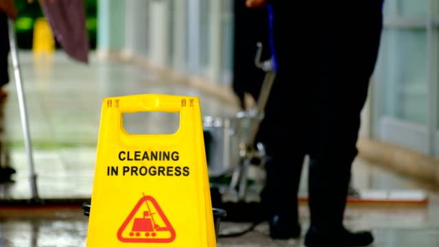 Équipe de service nettoyage sol avec machine de lavage et le nettoyage dans l'étiquette de la processus