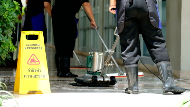 cleaning service team cleaning floor with scrubber machine and cleaning in process label - business finance and industry stock videos & royalty-free footage