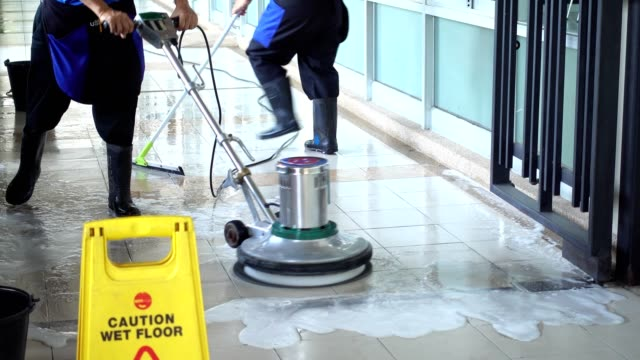 cleaning service team cleaning floor with scrubber machine and cleaning in process label - cleaner stock videos and b-roll footage